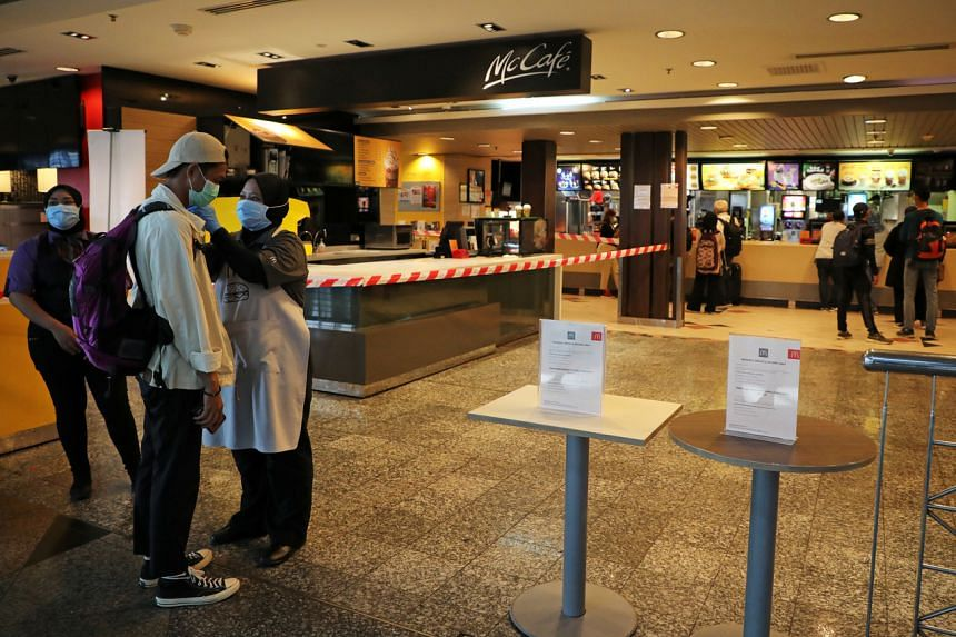 A McDonald's worker in Sepang taking the temperature of a customer on March 18, 2020, after Malaysia's government announced the movement control order to curb the spread of the coronavirus.