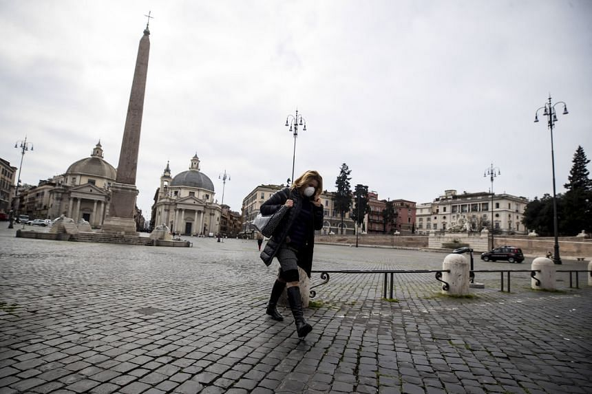 A woman with a protective mask walks across the Piazza del Popolo in Rome, Italy, on March 17, 2020.