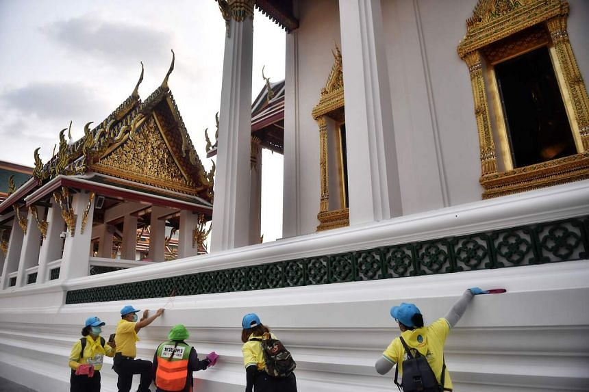 Volunteers and municipal workers clean surfaces at the Wat Suthat Thepwararam temple in Bangkok on March 17, 2020.