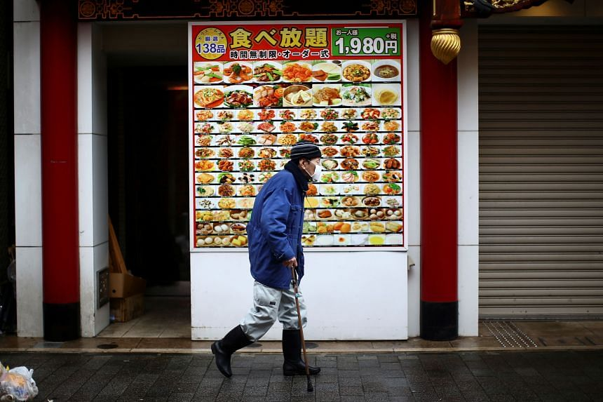 A man, wearing a protective mask following an outbreak of the coronavirus, walks on an almost empty street in Yokohama's Chinatown, south of Tokyo, on March 10, 2020.
