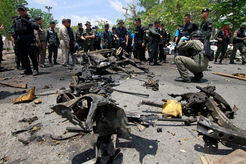 Security personnel at the site of a car bomb which exploded in front of the Thai government's Southern Border Provinces Administrative Centre in Yala yesterday. It was one of two bombs that went off in the area. There was no immediate claim of respon