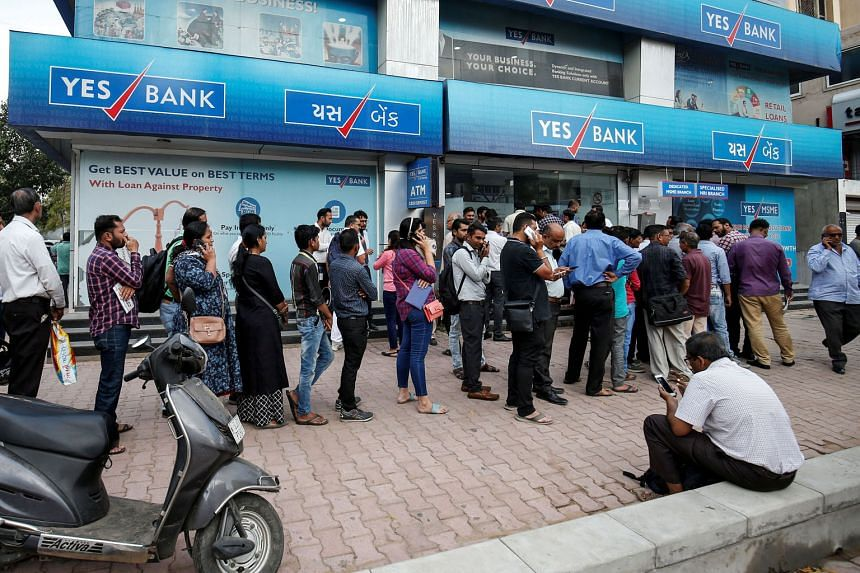Yes Bank founder Rana Kapoor arriving at the Enforcement Directorate office in Mumbai earlier this month. PHOTO: REUTERS People waiting outside a Yes Bank branch to withdraw their money in Ahmedabad, India. Earlier this month, India's central bank im