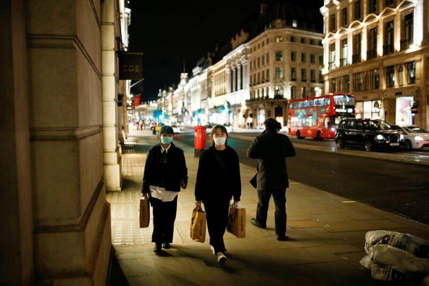 People wearing face masks walk down Regent Street in London on March 17, 2020.