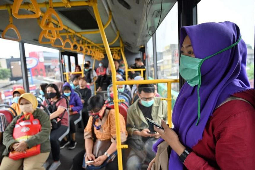 Indonesian passengers wearing face masks on a Trans Jakarta bus on March 18, 2020. The country announced 55 new coronavirus cases, taking the total to 227 in the South-east Asian nation and marking the biggest daily rise in positive cases.