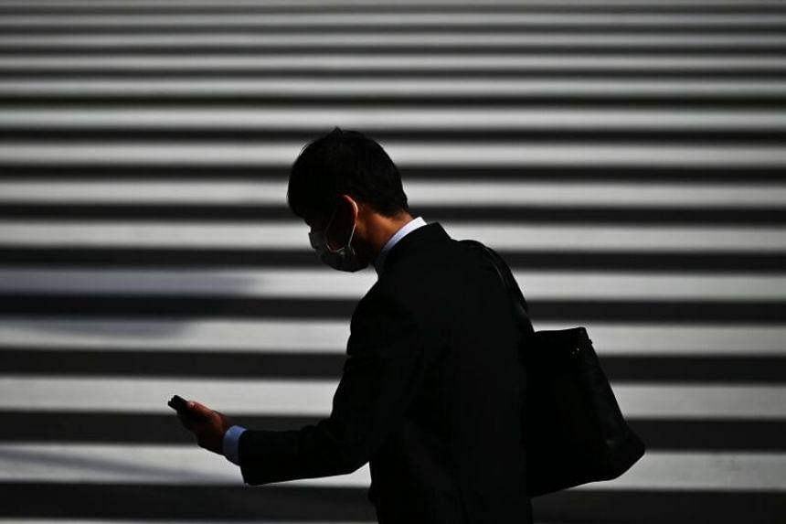 A man wearing a protective face mask crosses a street in Tokyo's Shimbashi area, on March 13, 2020.