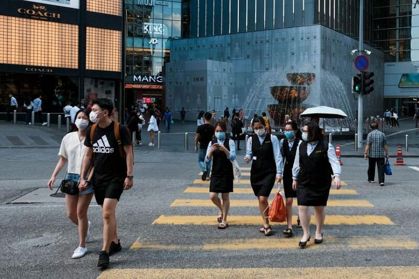 People wearing face masks, amid concerns over the spread of the coronavirus, cross a street next to commercial buildings in Kuala Lumpur, on March 16, 2020.