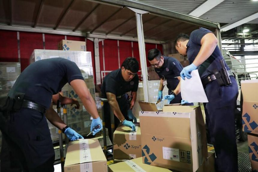 ICA officers inspecting items in the delivery trucks entering Singapore Cargo Clearance Centre at Woodlands checkpoint from Malaysia on March 18, 2020.