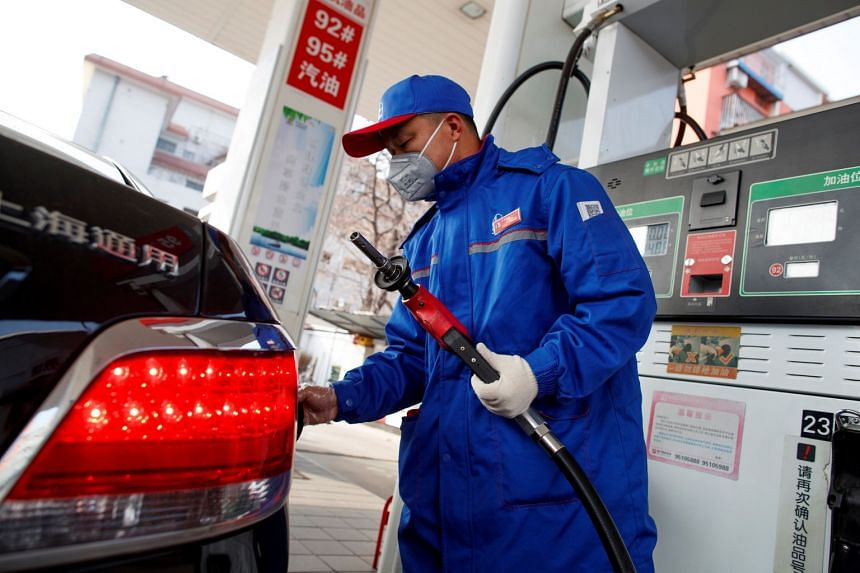 A pump attendant wears a mask as he refuels a car at a Sinopec gas station in Beijing, China, Feb 28, 2020.