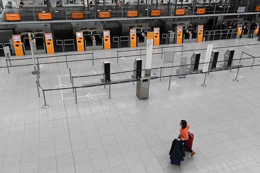 A woman wheeling her luggage through an empty check-in hall in Franz Josef Strauss airport in Munich, southern Germany, on Tuesday. Many flights have been cancelled by airlines because of the coronavirus and restrictions on travel by governments acro