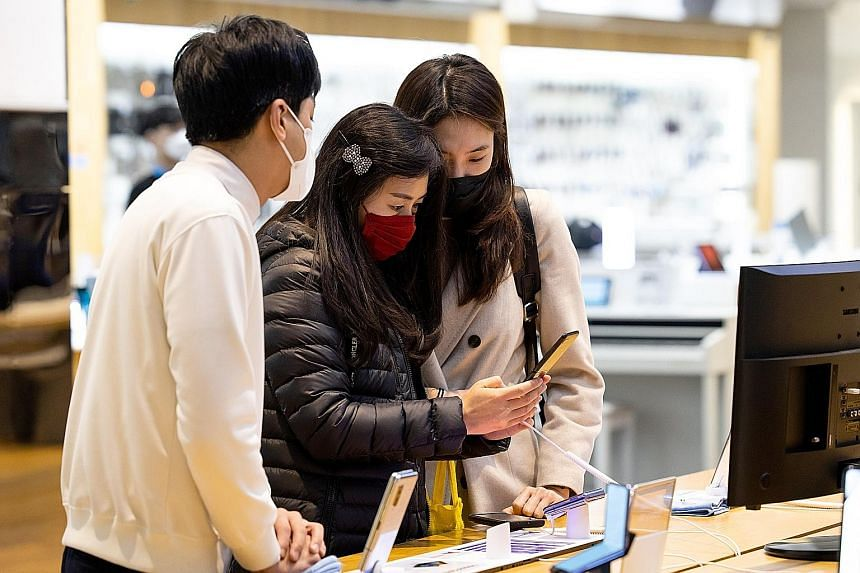An employee (far left) attending to customers at Samsung Electronics' D'light flagship store in Seoul earlier this month. Samsung expects the coronavirus pandemic to hurt sales of smartphones and consumer electronics this year.