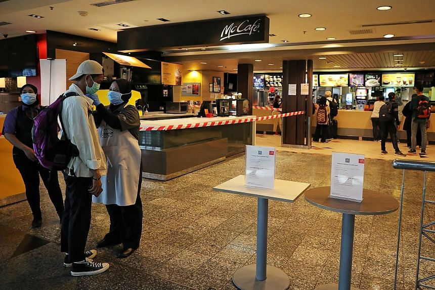 A customer having his temperature taken at a McDonald's outlet in Sepang yesterday before getting takeaway food. Dining in is not allowed. Businesses such as malls have to close, although essential service providers, such as eateries, supermarkets an
