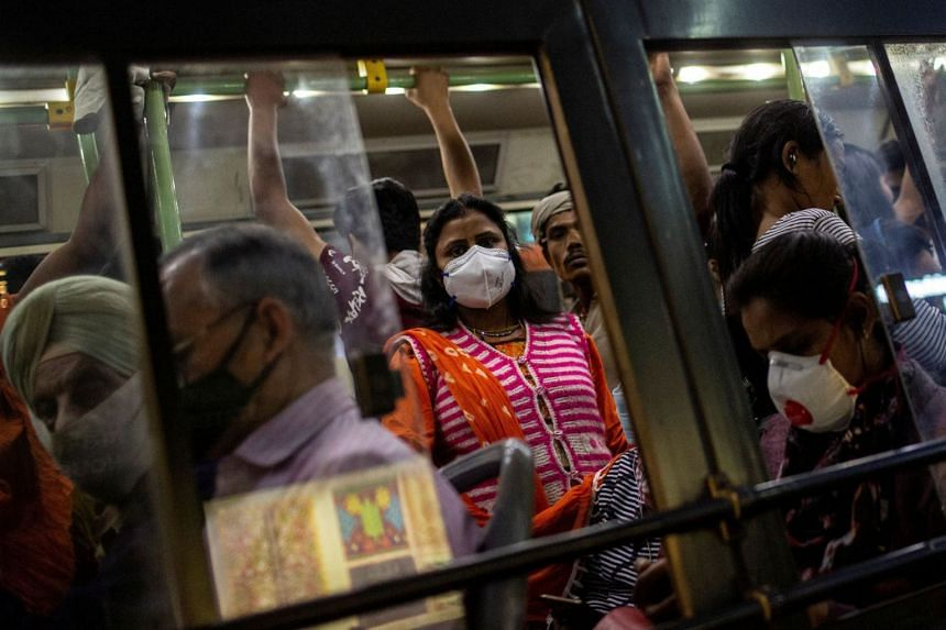 Commuters with protective masks travel in a crowded bus in New Delhi, on March 18, 2020.