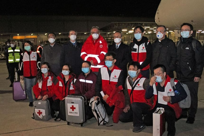 Chinese medics are seen after arriving from Shanghai at Rome's international airport to provide aid in curbing the spread of the coronavirus in Italy on March 13, 2020.
