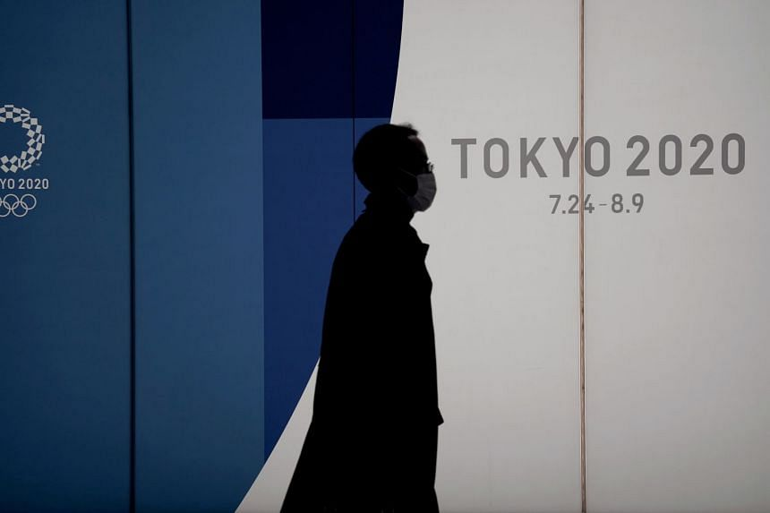 An office worker wearing a mask walks past a display promoting the Tokyo 2020 Olympics in Tokyo on March 18, 2020.