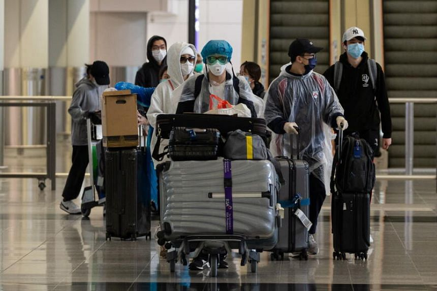 Travellers walk into the arrival hall of Hong Kong International Airport, on March 19, 2020.