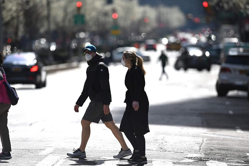 A couple wearing masks cross a street in New York on March 18, 2020.