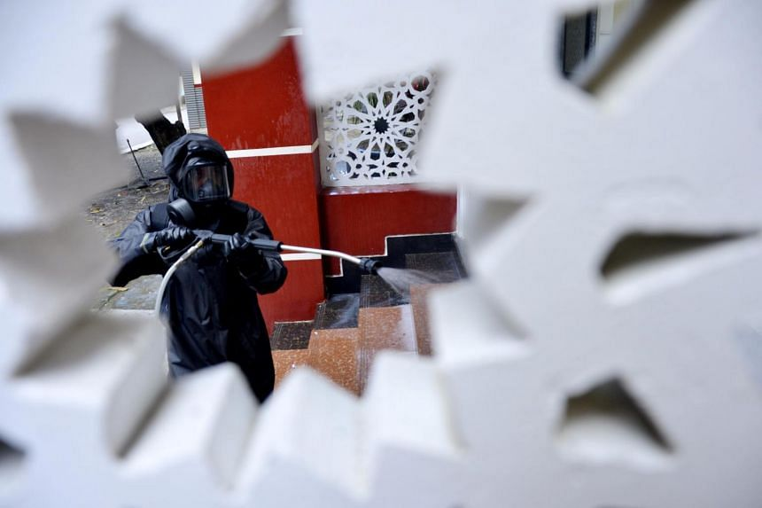A police officer wearing a protective suit sprays disinfectant at a mosque in Makassar, Indonesia, on March 16, 2020.