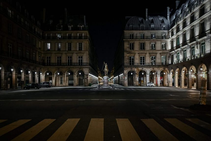 An empty intersection at night in Paris, after a lockdown was put in place, on March 18, 2020.