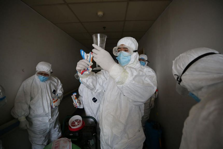 Workers prepare to disinfect rooms at the Red Cross hospital in Wuhan, in China's central Hubei province, on March 18, 2020.