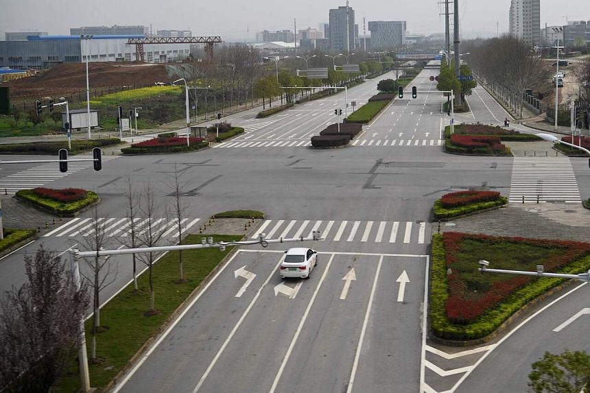 A car waits for the red light to change at an intersection in Wuhan on March 10, 2020.