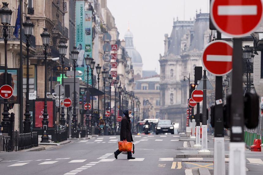 A man wearing a protective face mask crosses an empty Rue de Rivoli in Paris during a national lockdown on March 18, 2020. Countries are taking increasingly drastic steps to stem the flow of coronavirus infections.
