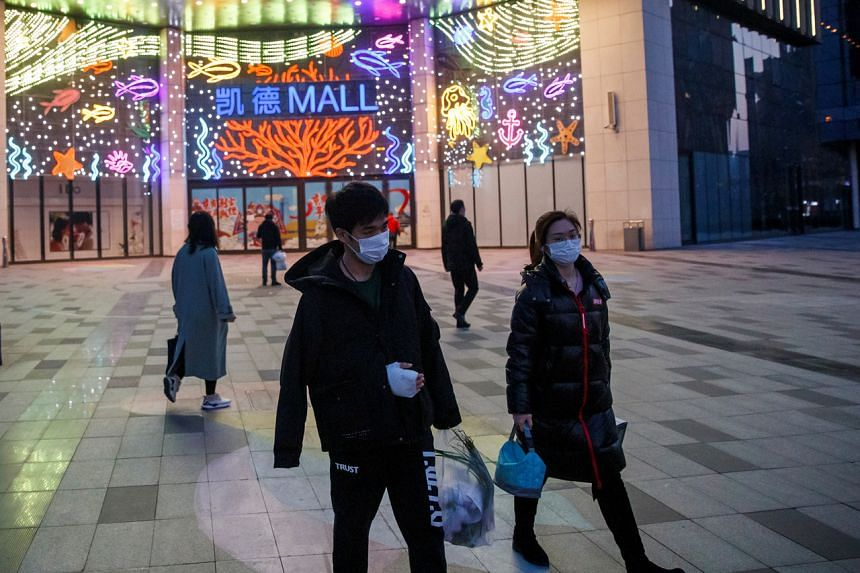 People wearing face masks outside a shopping mall in Beijing, on March 11, 2020.