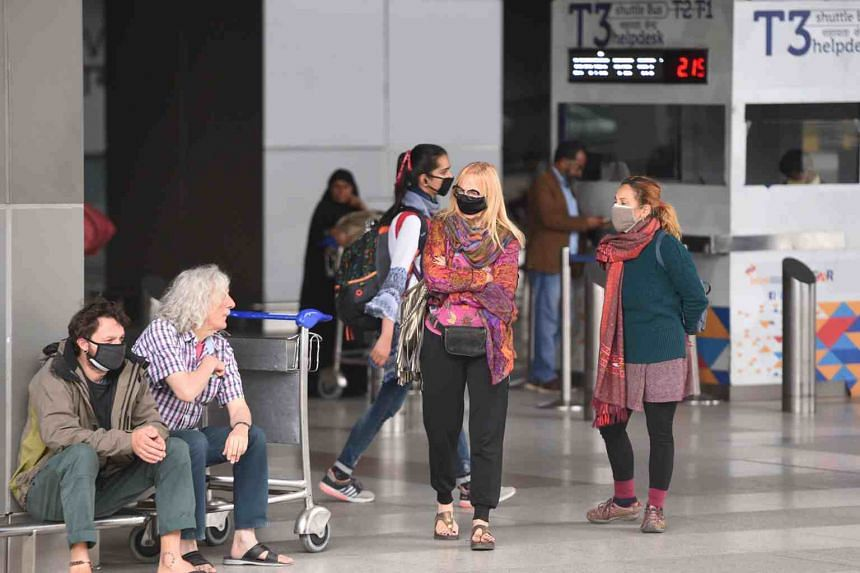 Passengers wearing face masks amid concerns over the spread of the coronavirus, stand outside the Indira Gandhi International Airport in New Delhi, on March 16, 2020.
