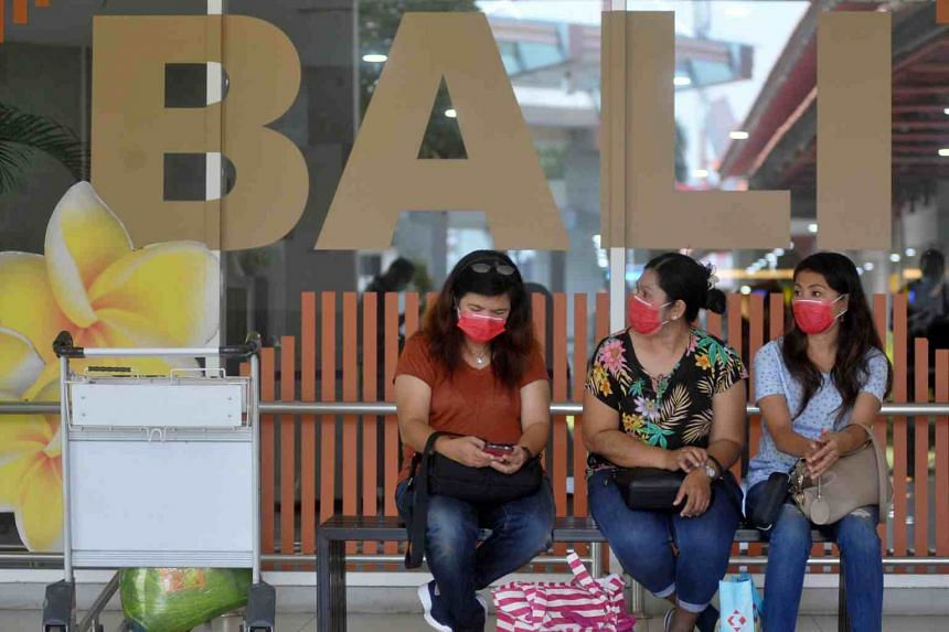 Passengers wear protective masks at a domestic departure terminal at Ngurah Rai International Airport in Bali, on March 13, 2020.