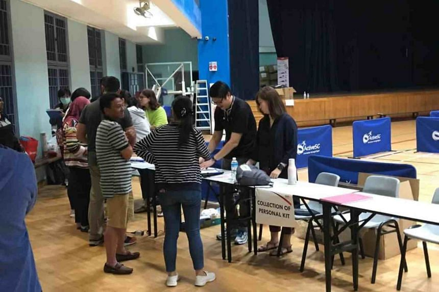 Malaysian workers checking in at a temporary relief centre managed by the Ministry of Social and Family Development at Jurong East, which was repurposed from a sports hall.