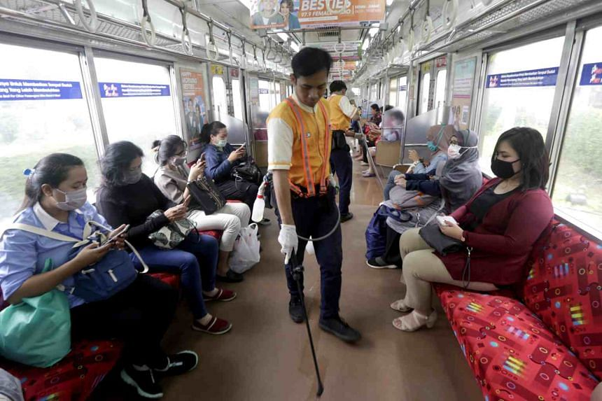 A worker sprays disinfectant on an MRT train in Jakarta on March 19, 2020.