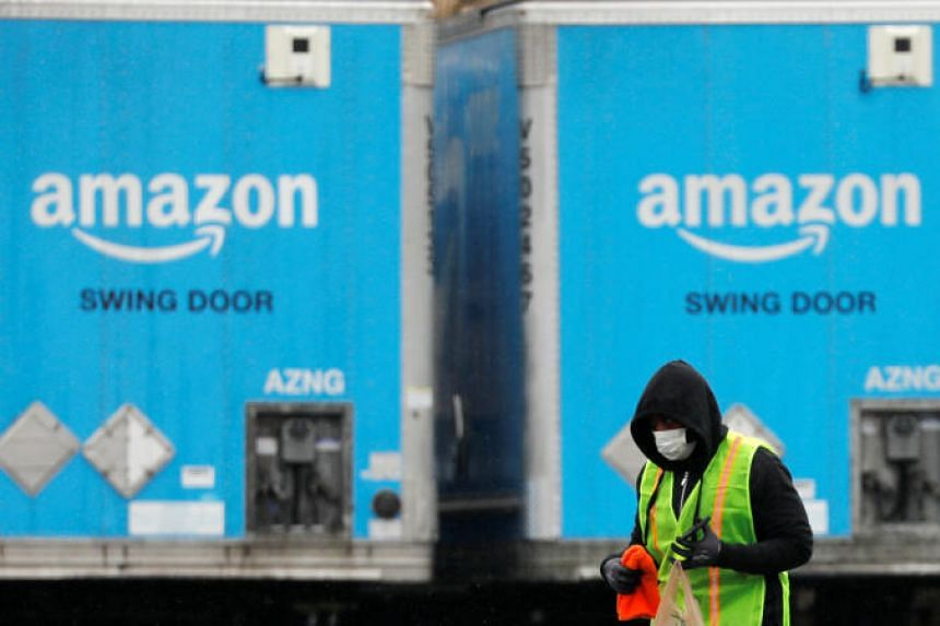 A worker in a face mask walks by trucks parked at an Amazon facility in New York, on March 17, 2020.