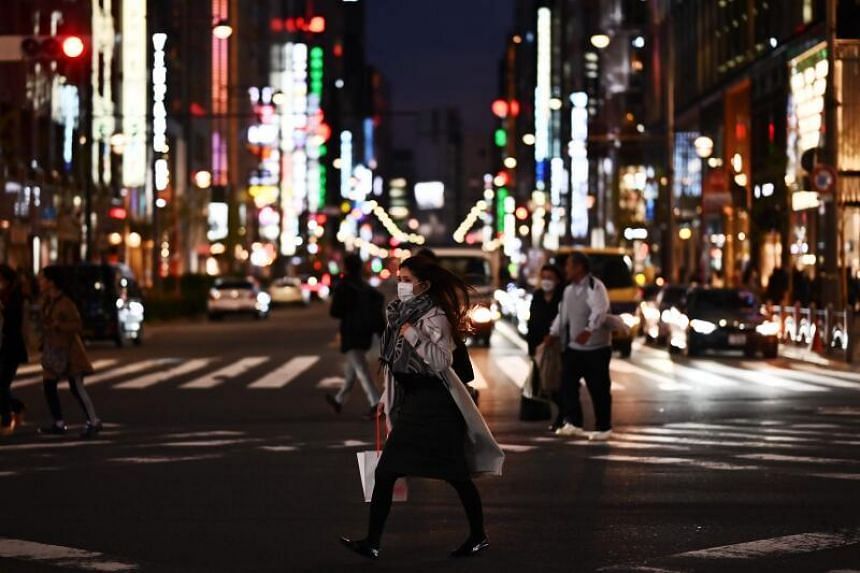 People wearing face masks, amid the coronavirus outbreak, cross a street in Tokyo's Ginza area on March 18, 2020.