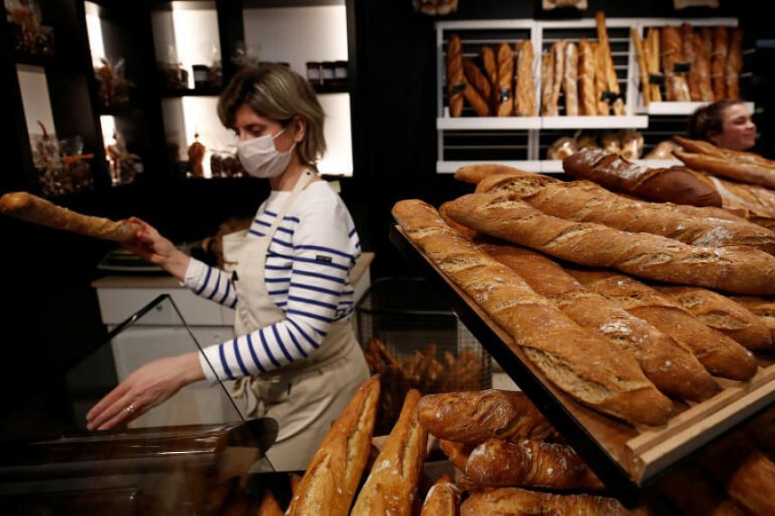 "An employee wearing a protective face mask serves a baguette at the bakery ""Ma Boulangerie"" in Vertou, near Nantes as France faces the coronavirus disease outbreak, on March 17, 2020."