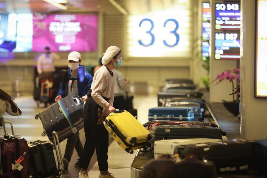 People arriving in Singapore from New York at the baggage claim area in Changi Airport on March 19, 2020.