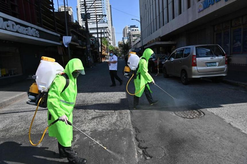 City workers wearing protective suits disinfect a street, as a preventive measure against the Covid-19 coronavirus, in Manila, on March 19, 2020.