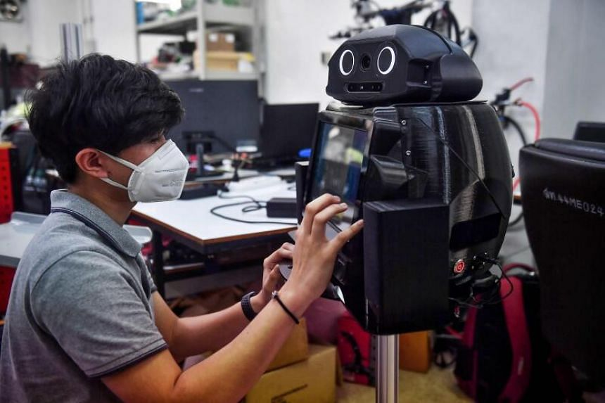 An engineering student configures a medical robot modified to screen and observe Covid-19 patients at the Regional Centre of Robotics Technology at Chulalongkorn University in Bangkok, on March 18, 2020.