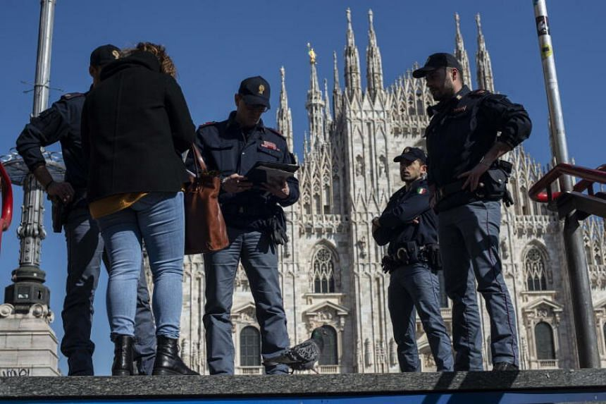 Italian police perform checks at the Piazza del Duomo during the coronavirus outbreak in Milan, on March 18, 2020.