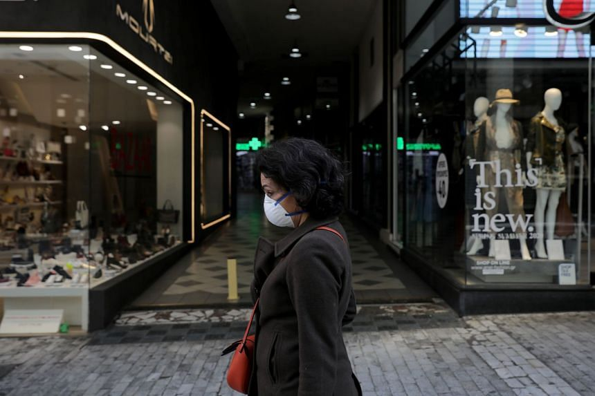 A woman in a protective mask walks outside a closed store on the main commercial Ermou Street in Athens.