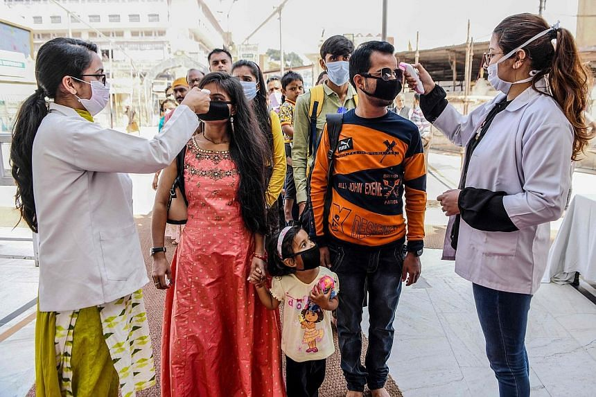 Health workers checking the temperature of devotees at the entrance of the Durgiana Temple in Amritsar in the northern Indian state of Punjab on Wednesday. The state, which saw India's fourth coronavirus fatality yesterday, has suspended public trans