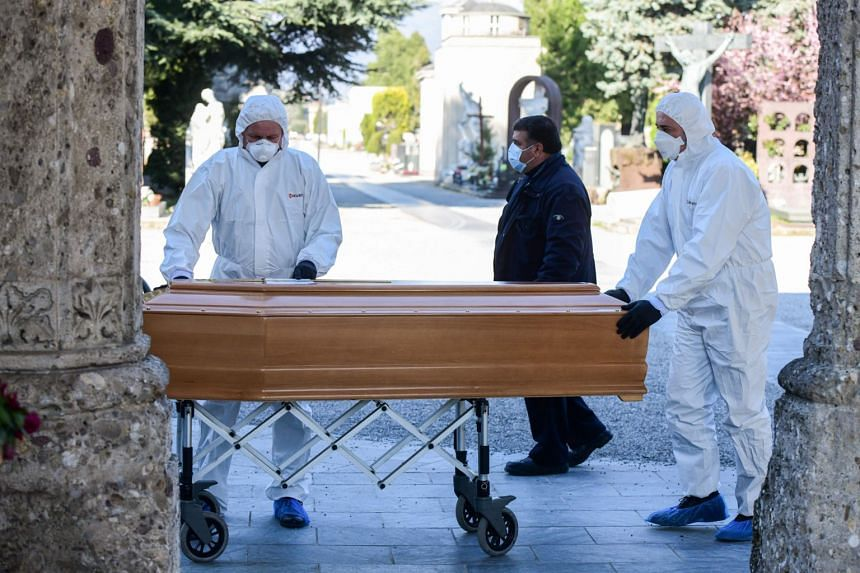 Undertakers wearing a face mask and overalls unload a coffin out of a hearse in Lombardy, Italy, on March 16, 2020.