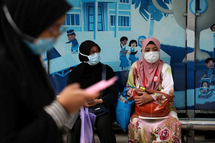 People wearing protective face masks wait for a bus at a bus station in Kuala Lumpur, Malaysia, on Feb 19, 2020. The price of the three-ply face mask will now cost RM2 (66 Singapore cents) instead of 80 sen per piece.