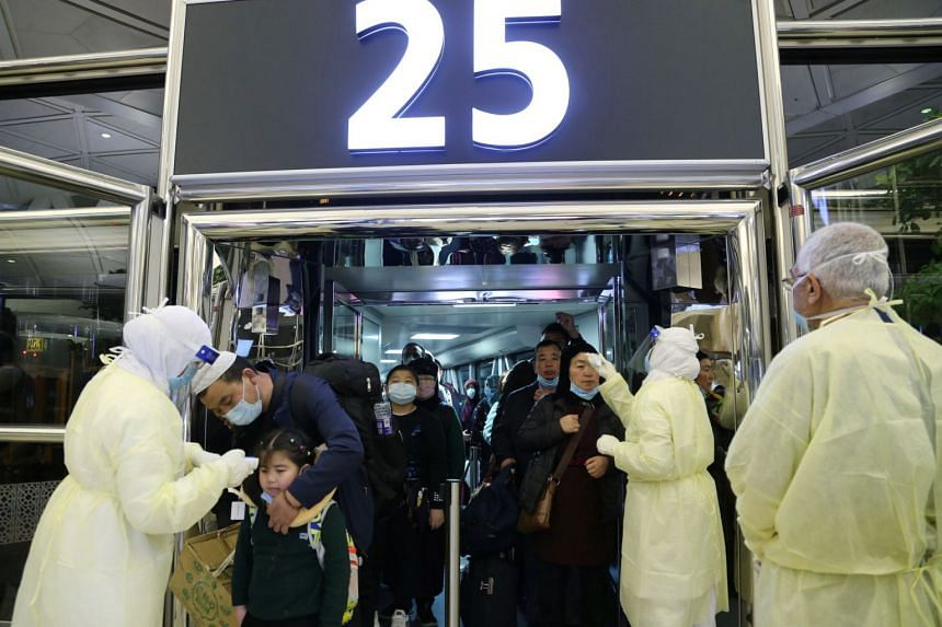 In a photo taken on Jan 29, 2020, passengers from China are checked by Saudi Health Ministry employees upon their arrival at King Khalid International Airport, in Riyadh, Saudi Arabia.