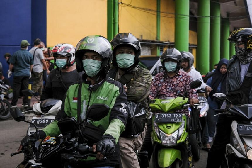 People wear protective face masks as they ride on their motorbikes outside a market in Jakarta, Indonesia, on March 20, 2020.