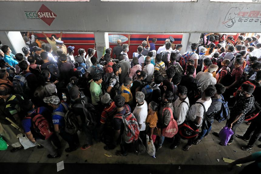 People waiting for buses to take them home after the government announced a curfew over the weekend in Colombo, Sri Lanka, on March 20, 2020.