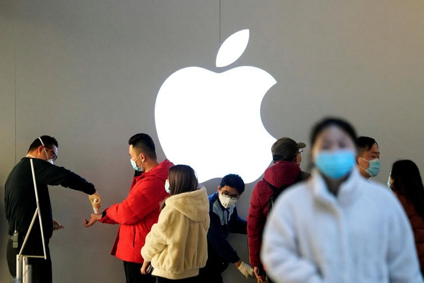 In a photo from Feb 21, 2020, people wearing protective masks wait to have their temperature checked in an Apple Store in Shanghai.