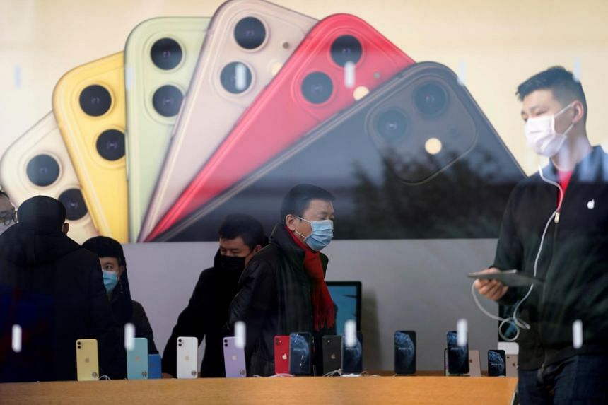 People wearing protective masks are seen in an Apple Store, in Shanghai, China, on Jan 29, 2020.