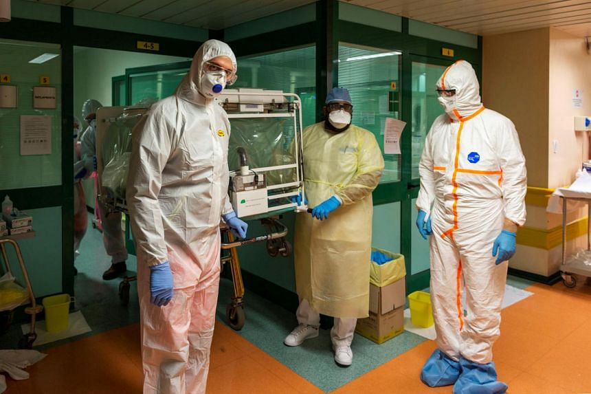 Medical workers transfer a coronavirus patient from the intensive care unit of the Gemelli Hospital to the Columbus Covid Hospital, in Rome, Italy, on March 16, 2020.