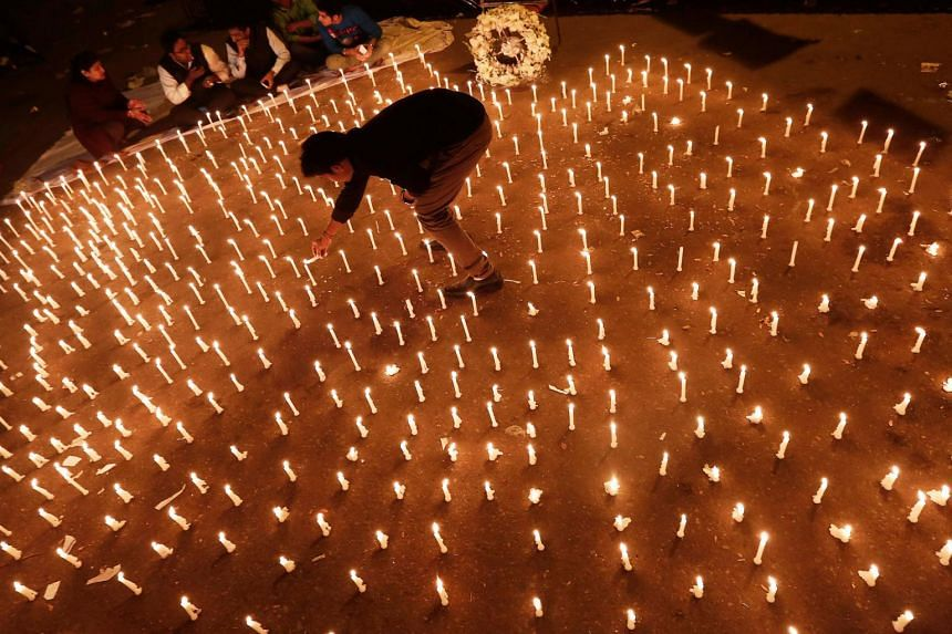 In a photo from Dec 16, 2013, a protester lights candles during a candlelight vigil to mark the first anniversary of the Delhi gang rape, in New Delhi.
