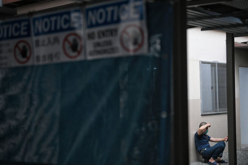In a photo from March 5, 2020, a foreign worker under stay-home notice uses his handphone at a segregated area at the CDPL Tuas Dormitory.