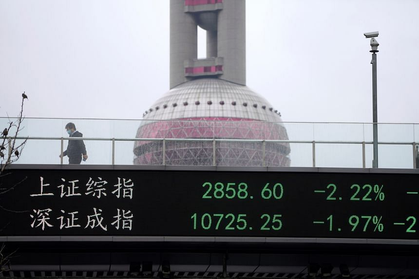 A man wearing a face mask walks by an electronic board showing the Shanghai and Shenzhen stock indexes, in Shanghai, China, on March 13, 2020.
